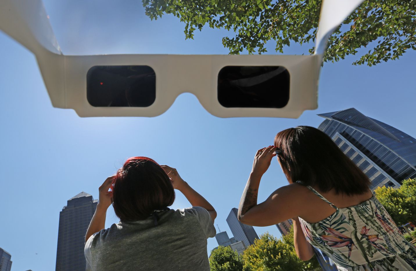 Rose Chavez and Adri Robles watched the solar eclipse through special sunglasses at Klyde Warren Park in Dallas on Monday. (Louis DeLuca/Staff Photographer)