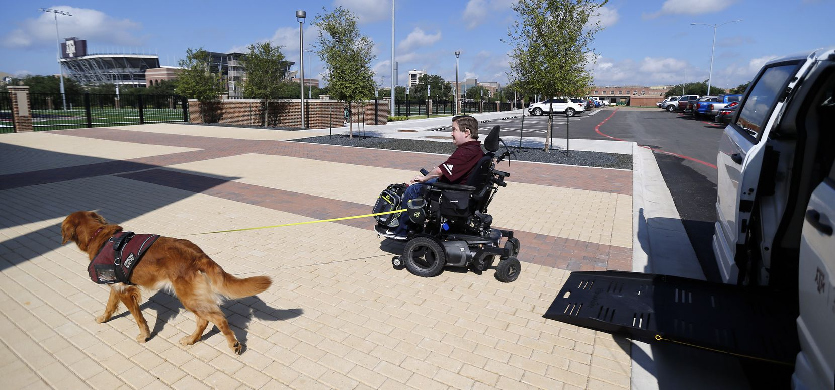 Texas A&M graduate student Kyle Cox, who has Duchenne Muscular Dystrophy, and his golden retriever service dog, Amber, head to symphonic band rehearsal at the new Music Activities Center on the Texas A&M campus in College Station, Texas, Wednesday, September 11, 2019. Kyle receives a ride to classes in a specially equipped university van.