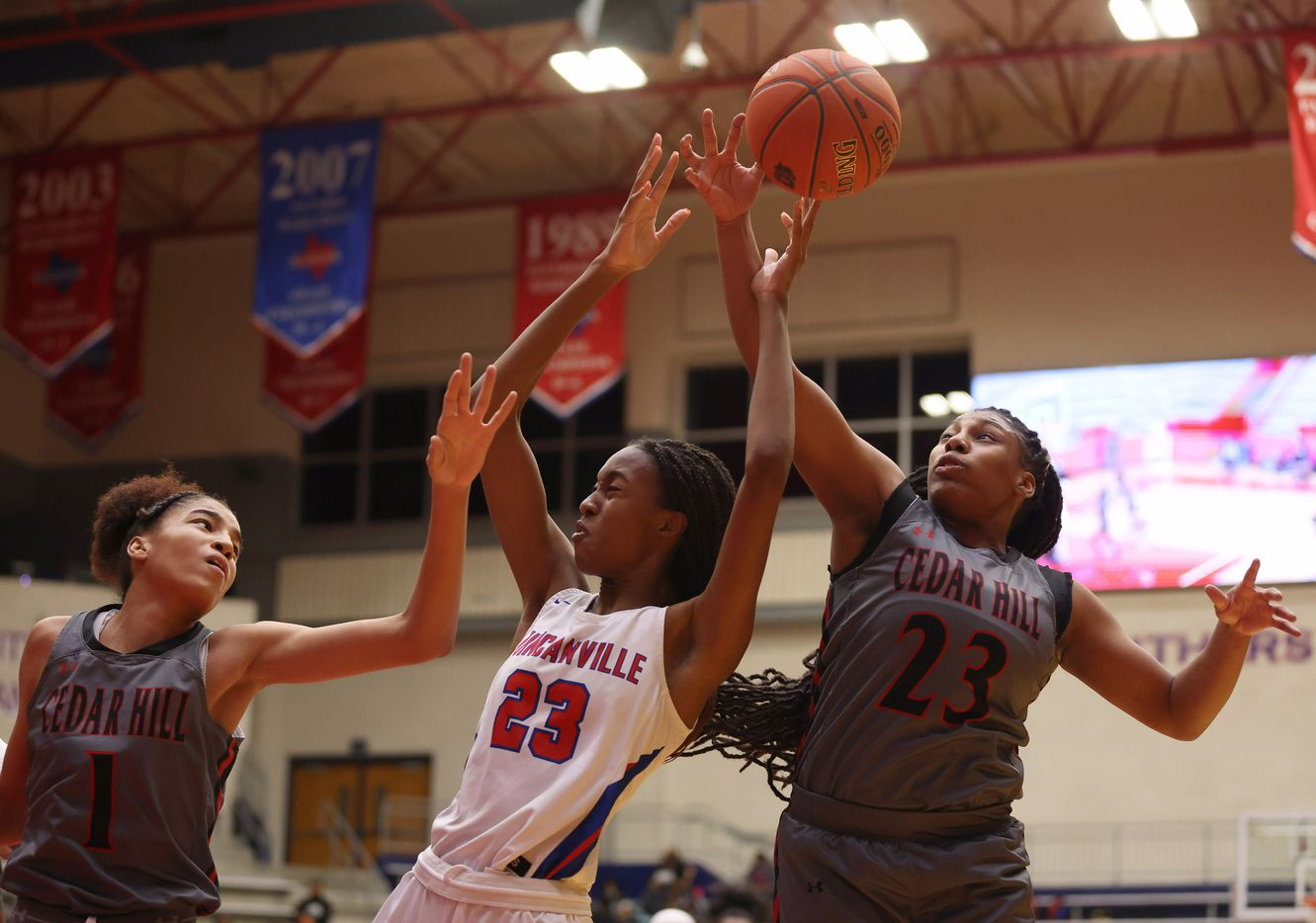 Duncanville's Kiersten Johnson (23), Cedar Hill's Jadyn Atchison (1) and Cedar Hill's Theasia Ebron (23) go after a rebound during the first half of play at Sandra Meadows Arena at Duncanville High School on Tuesday, January 12, 2021 in Dallas. (Vernon Bryant/The Dallas Morning News)