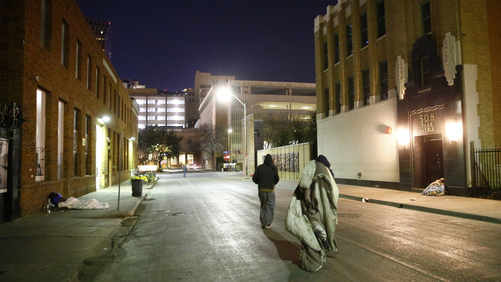 People move their blankets down Park Avenue next to The Stewpot in downtown Dallas. Temperatures are sinking well below zero overnight this week.