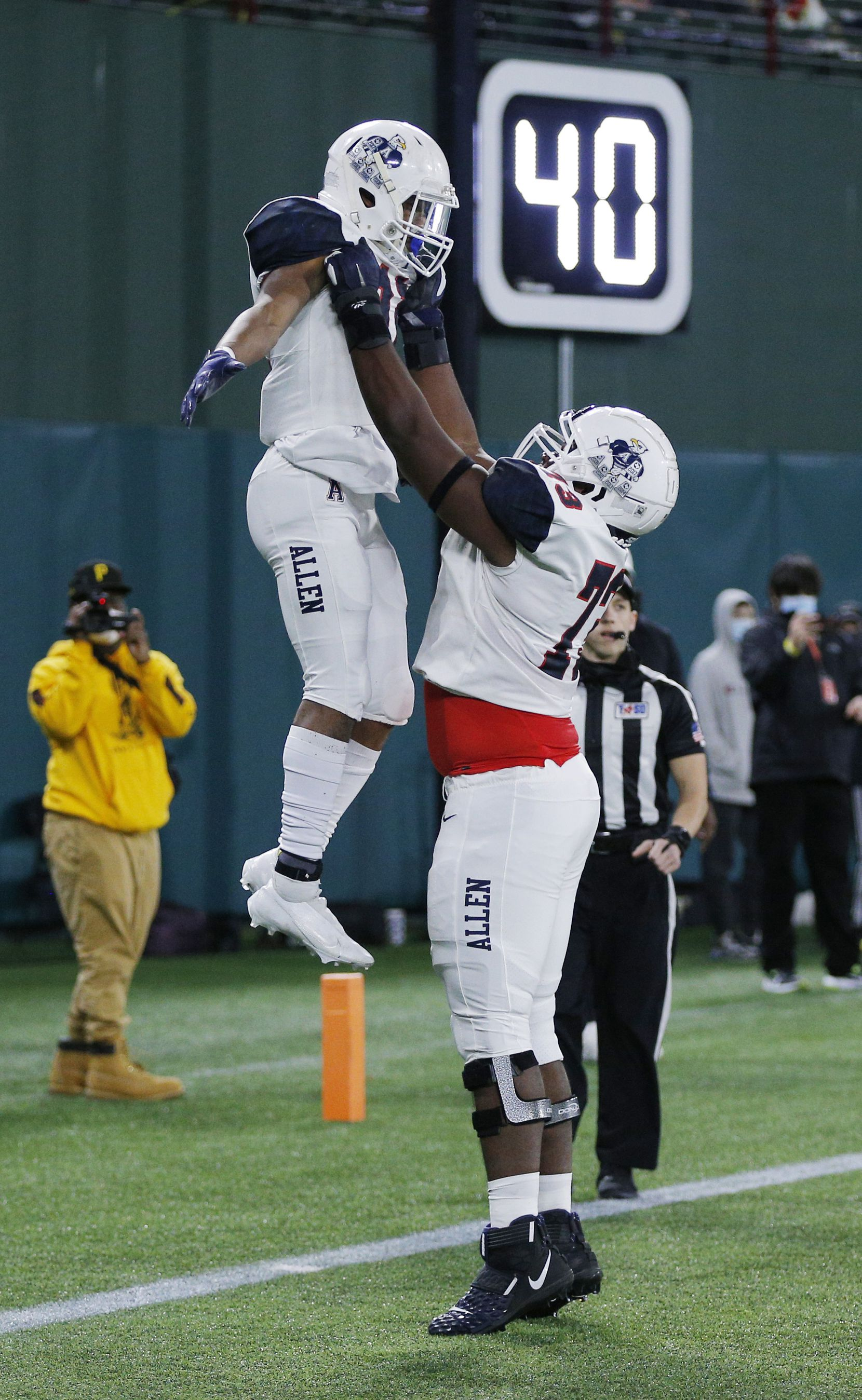 Allen senior vide receiver Jordan Johnson (11) is lifted into the air after scoring a touchdown by junior offensive lineman Neto Umeozulu (73) during the first half of a high school Class 6A Division I Region I semifinal football game against Euless Trinity at Globe Life Park in Arlington, Saturday, December 26, 2020. (Brandon Wade/Special Contributor)