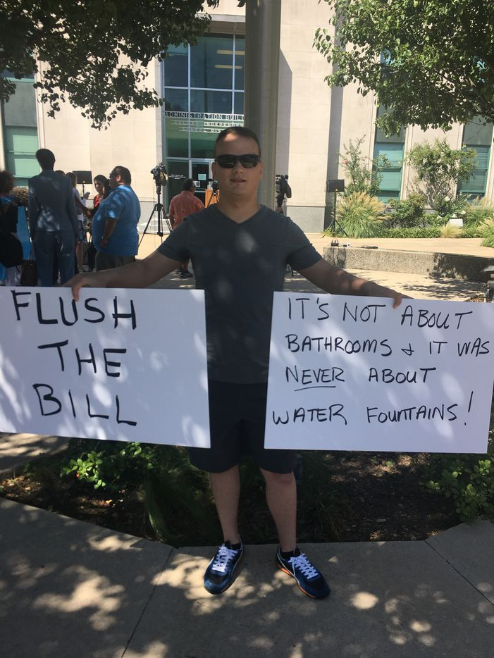 Justin Culpepper holds two signs at a demonstration against Texas' so-called bathroom bill.