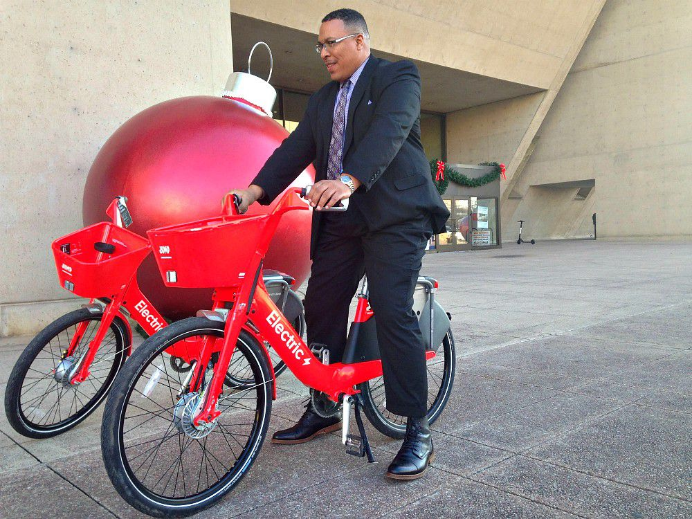 Michael Rogers, Dallas' director of transportation, test-spins a Jump in front of Dallas City Hall Monday afternoon