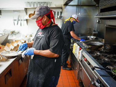 Cruz Garcia (front) and Eduardo Garcia wear face masks as they work in the kitchen at TJ's Seafood restaurant on Tuesday, May 19, 2020, in Dallas.