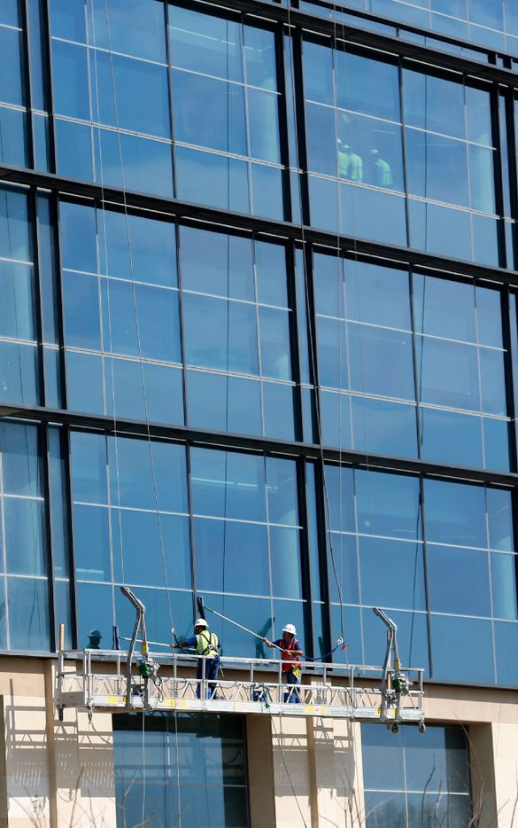 Workers wash windows as construction continues at the new Toyota headquarters in Plano on Wednesday, March 8, 2017. (Vernon Bryant/The Dallas Morning News)
