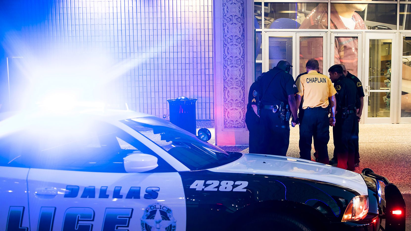 At 8:53 p.m., five minutes before the shooting began exactly one year earlier, Dallas police officers joined Dallas County Community College District police in prayer on July 7, 2017, in front of the Lamar Street entrance to El Centro College.