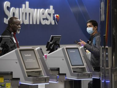 "A Southwest Airlines employees helps a passenger wearing a facial mask at LaGuardia Airport, Saturday, March 21, 2020, in New York, N.Y. The Federal Aviation Administration briefly suspended flights to New York City-area airports on Saturday after a trainee at a regional air-traffic control hub on Long Island tested positive for coronavirus. In an alert posted online, the FAA advised air traffic controllers to ""stop all departures"" to John F. Kennedy, LaGuardia, Newark and other airports in the region because of staffing issues at the Ronkonkoma facility, which the agency says primarily handles high-altitude, cross-country flights. (AP Photo/Mary Altaffer)"