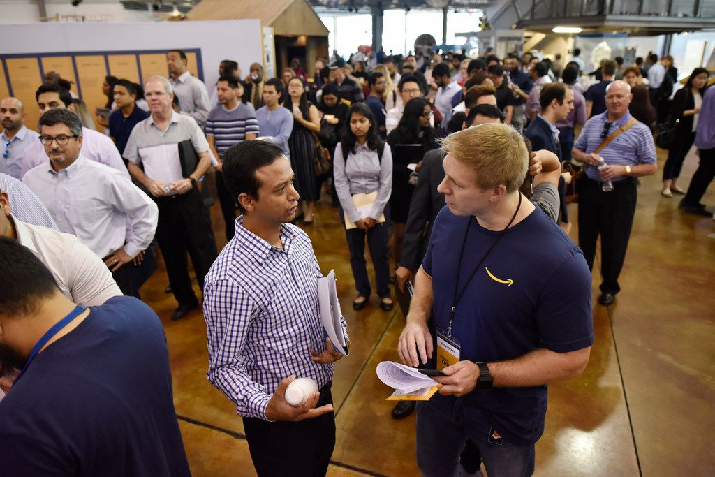 Sujan Shrestha, 35, left, of Dallas, meets with Jamin Taylor, right, an Amazon business development recruiting manager, during the job fair at the Frontiers of Flight Museum.