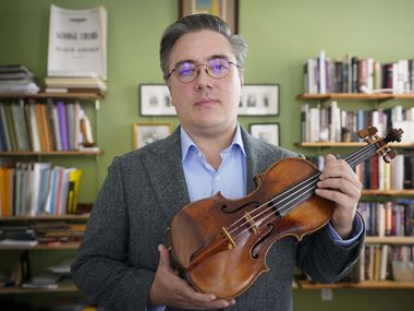 SMU professor Aaron Boyd poses with his violin on Thursday.