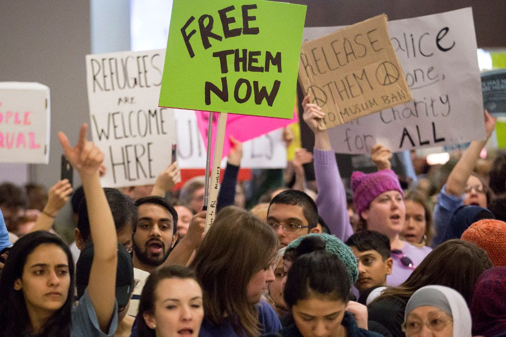 Protestors at DFW International Airport chant in opposition to President Donald Trump's executive order barring certain travelers on Sunday, Jan. 29, 2017. Multiple travelers were detained at DFW after Trump shuts borders. (Smiley N. Pool/The Dallas Morning News)