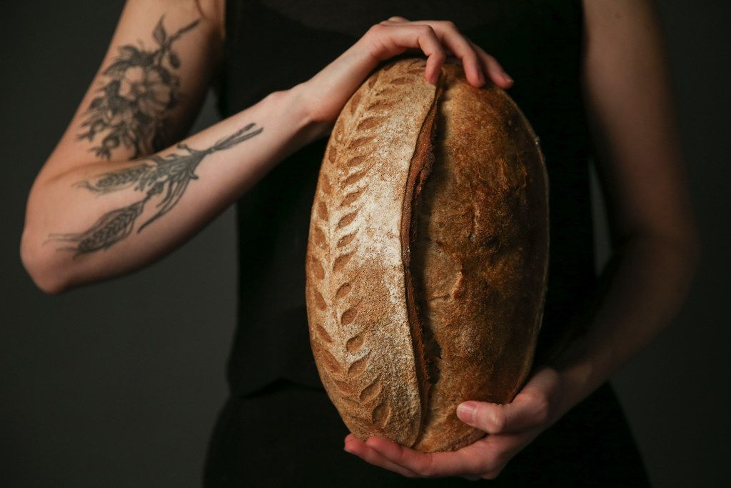 Brooke Carter of Rosemary Bakery is photographed holding loaves of fresh sourdough bread on July 17, 2019 in The Dallas Morning News Test Kitchen in Dallas. (Ryan Michalesko/The Dallas Morning News)