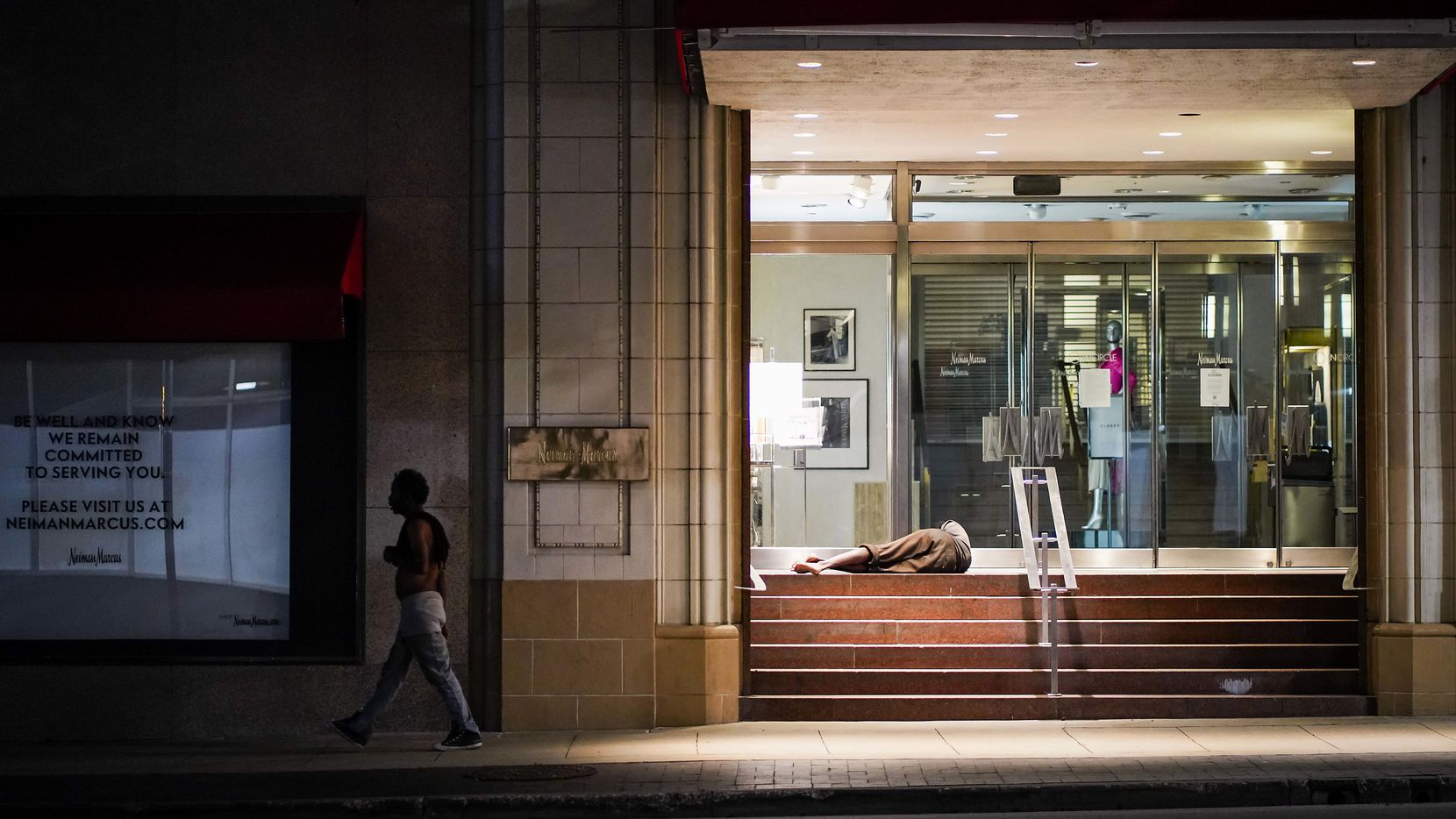 A homeless man sleeps in the doorway of the Neiman Marcus flagship store in downtown Dallas on Thursday, May 7, 2020.