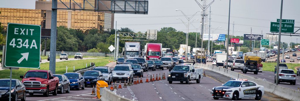 Traffic is routed off the interstate as Texas Department of Transportation employees work to clean up after a truck transporting rocks was involved in an accident on Sept. 7, 2018 on I-35E southbound in Dallas.