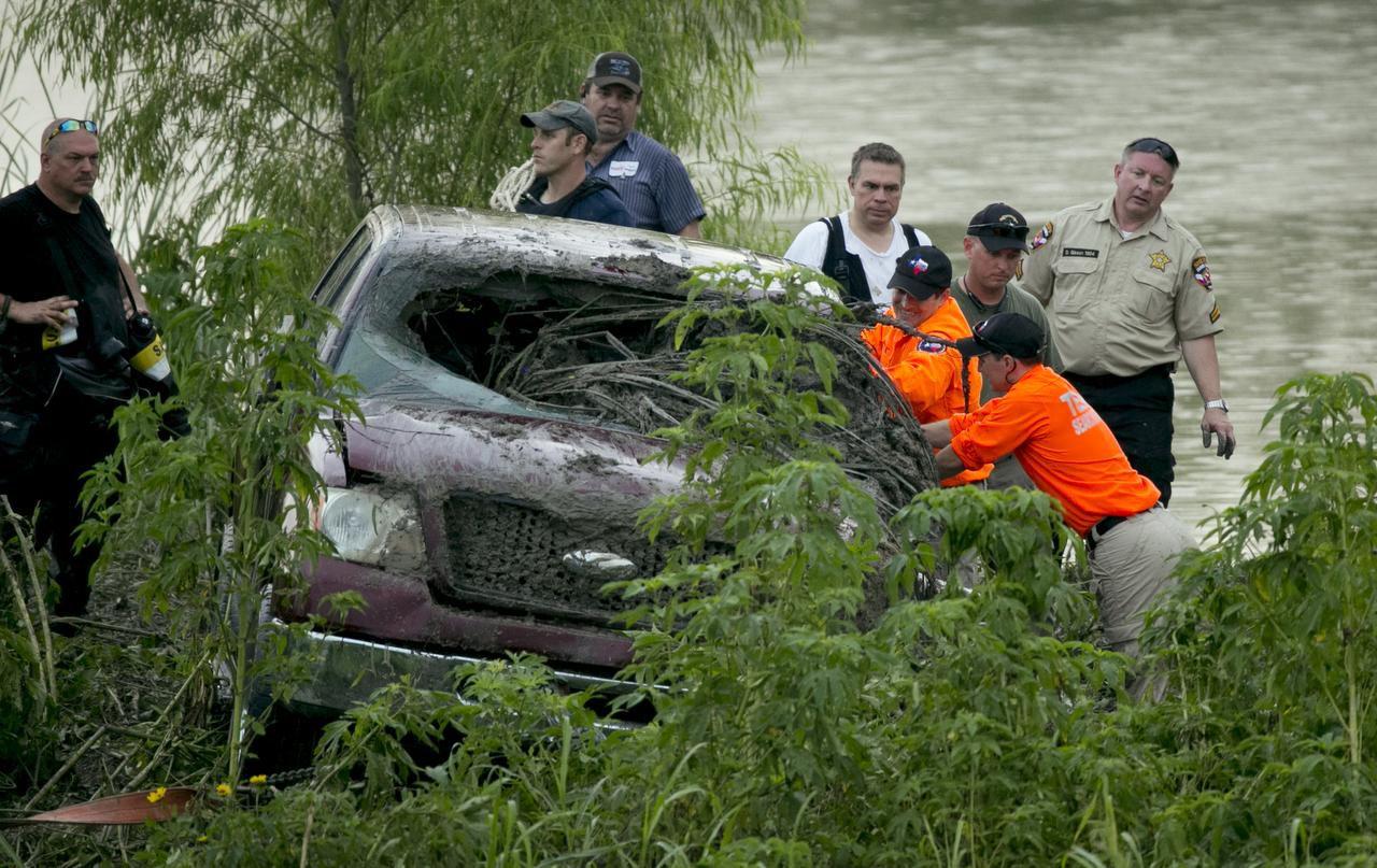 Rescatistas revisan una camioneta arrastrada por el agua de una inundación cerca de un estanque en Austin. La víctima aún no ha sido localizada. (AP/JAY JANNER)