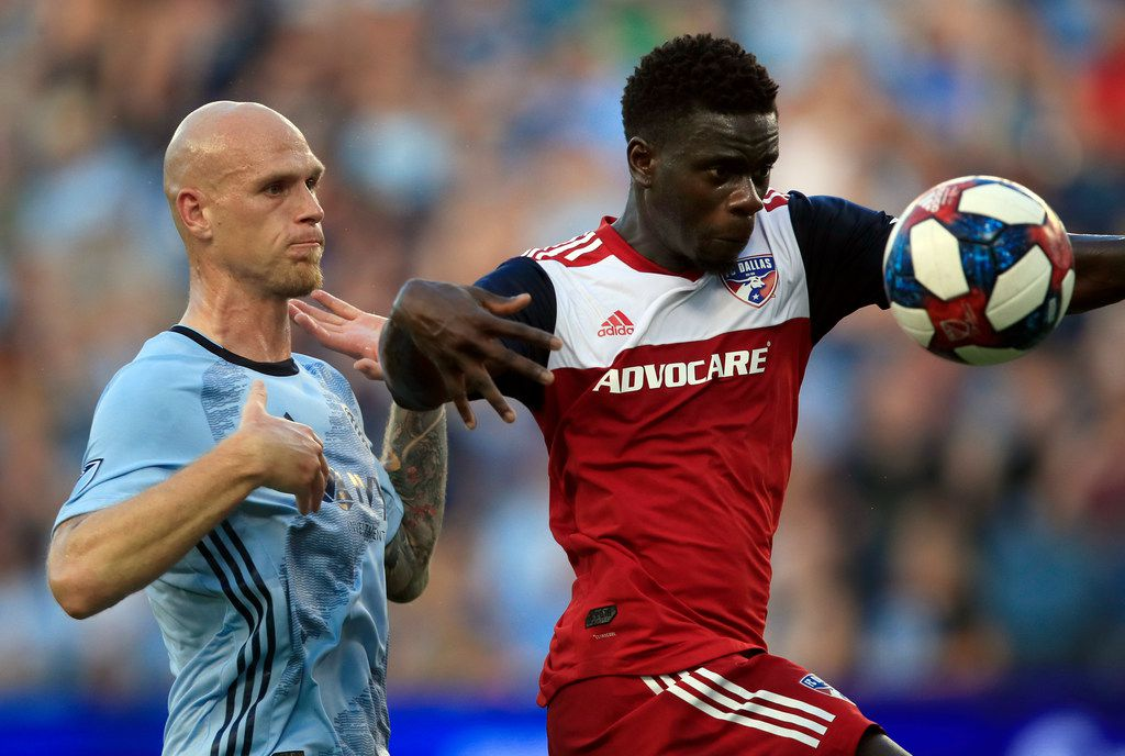 FC Dallas forward Dominique Badji, right, plays the ball in front of Sporting Kansas City defender Botond Barath, left, during the first half of an MLS soccer match in Kansas City, Kan., Saturday, July 20, 2019. (AP Photo/Orlin Wagner)