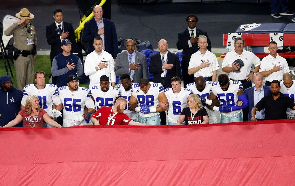 Dallas Cowboys link arm in arm during the National Anthem prior to the start of a game against the Arizona Cardinals at University of Phoenix Stadium in Glendale, Arizona on Monday, September 25, 2017. (Vernon Bryant/The Dallas Morning News)