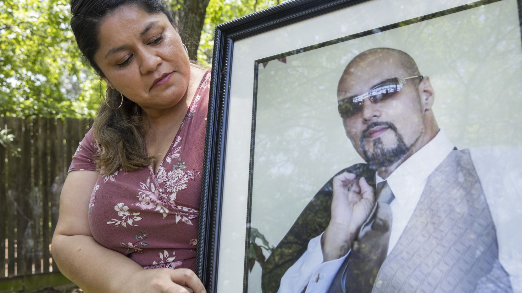 Parkland Health & Hospital System nurse Dolores Diaz poses for a photo with a photo of her late husband on July 9, 2020 at their home in Grand Prairie. Dolores' husband Juan died unexpectedly in late June.(Juan Figueroa/ The Dallas Morning News)