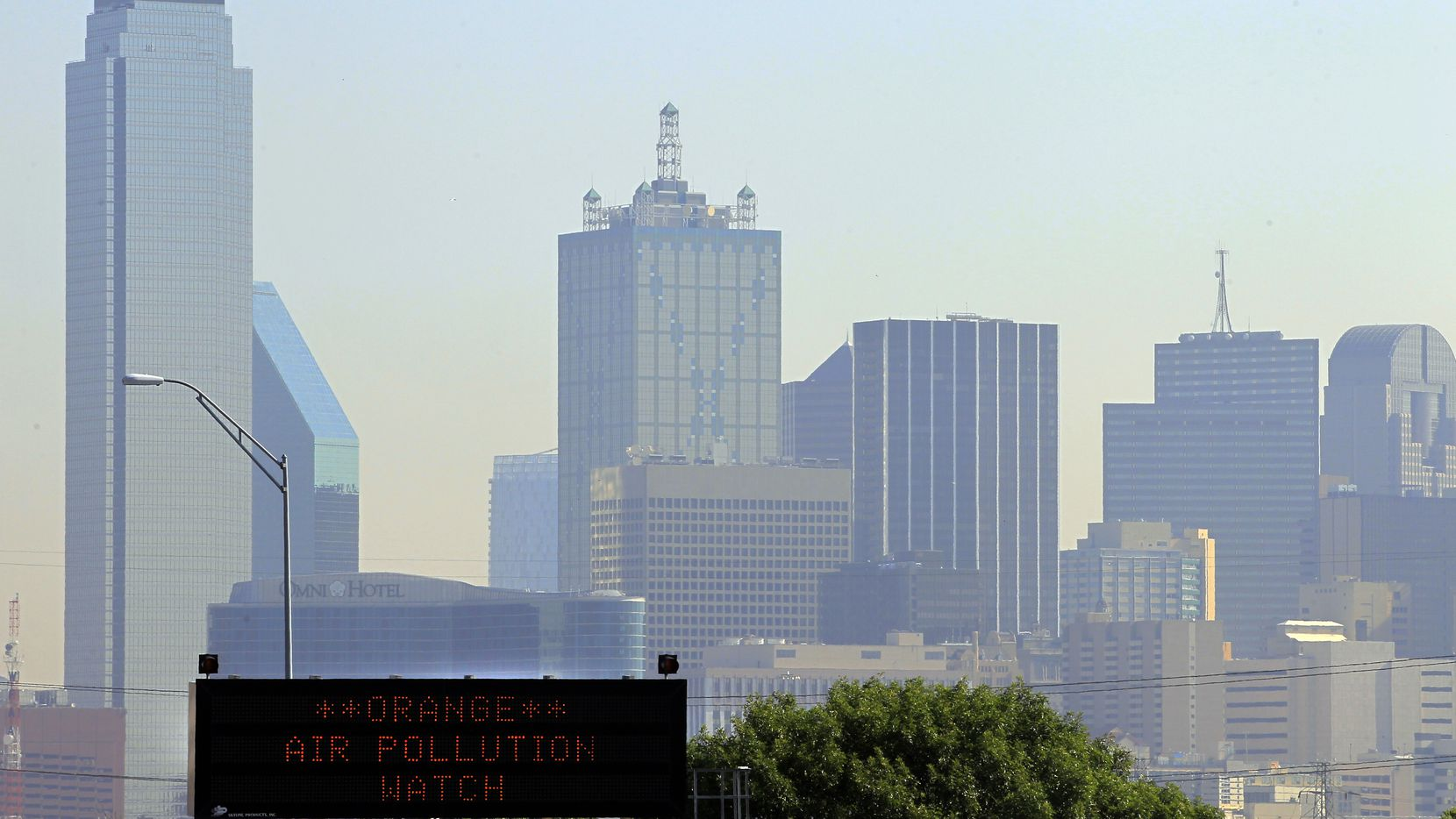 A highway sign alerts drivers on Interstate 35E to high air pollution conditions in Dallas.