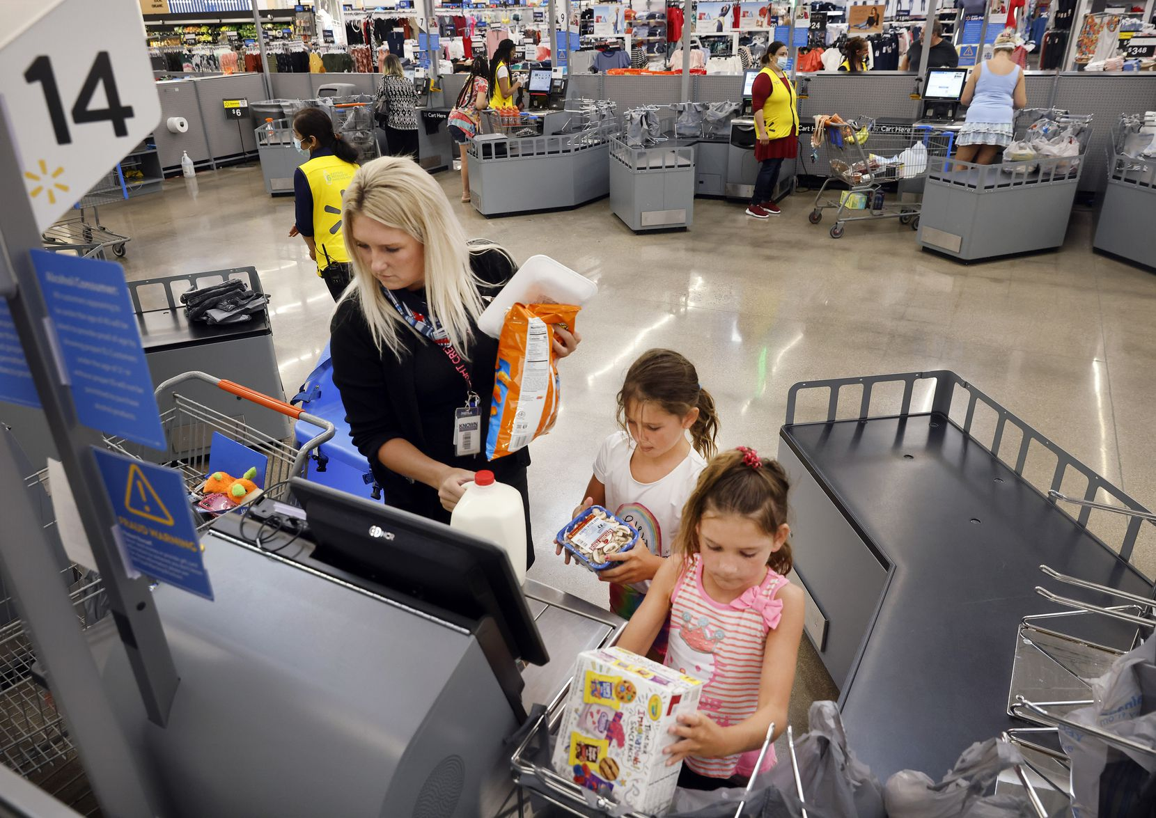 Breanna Hale of Frisco receives some help from her daughters, Burklee (center) and Ellasyn, who bag her scanned items at the Walmart Supercenter on Ohio Drive in Plano. The store is testing a large corral of self checkout stations with a big open space in the middle where the old cashier lanes used to be.