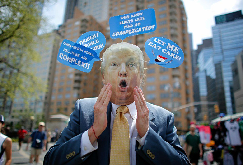 A man wears a mask with the face of US President Donald Trump, as he takes part in the '100 Days of Failure' Protest to mark the first 100 days of the Trump administration on April 29, 2017 in New York.