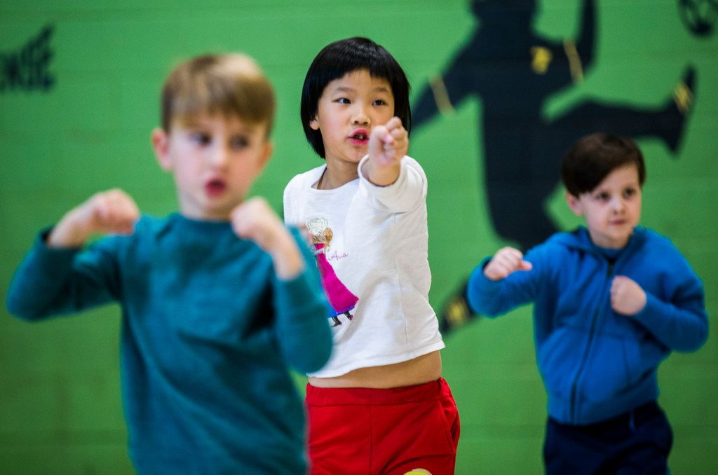 Pink Elementary School kindergarteners (from left) J.D. Klinge, Lannie Wo and Griffin Peach take part in a martial arts class.