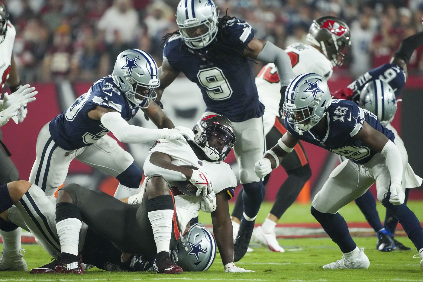 Tampa Bay Buccaneers running back Leonard Fournette (7) is brought down by Dallas Cowboys linebacker Leighton Vander Esch (55) along with cornerback Anthony Brown (30), linebacker Jaylon Smith (9) and safety Damontae Kazee (18) during the first half of an NFL football game  at Raymond James Stadium on Thursday, Sept. 9, 2021, in Tampa, Fla. (Smiley N. Pool/The Dallas Morning News)