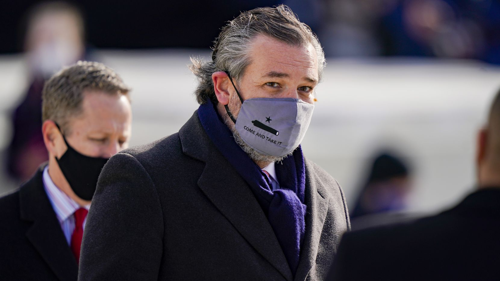 """Sen. Ted Cruz, wearing a face mask that reads """"Come and Take It,"""" arrives to the inauguration of President Joe Biden on the West Front of the U.S. Capitol on January 20, 2021."""