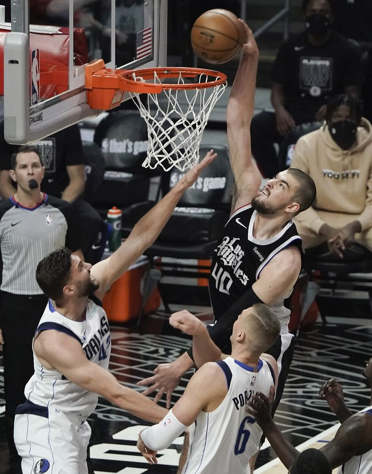 LA Clippers center Ivica Zubac (40) dunks the ball past Dallas Mavericks forward Maxi Kleber (42) and center Kristaps Porzingis (6) during the first half of an NBA playoff basketball game at Staples Center on Saturday, May 22, 2021, in Los Angeles.