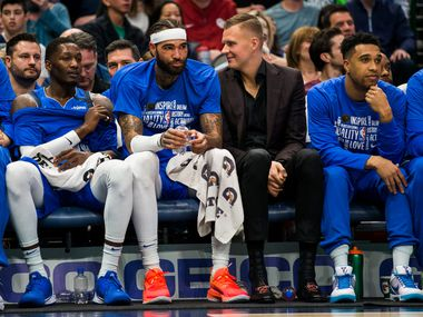 Dallas Mavericks forward Kristaps Porzingis (6) sits on the bench in a suit next to Dallas Mavericks center Willie Cauley-Stein (33) during the first quarter of an NBA game between the Dallas Mavericks and the Atlanta Hawks on Saturday, February 1, 2020 at American Airlines Center in Dallas.