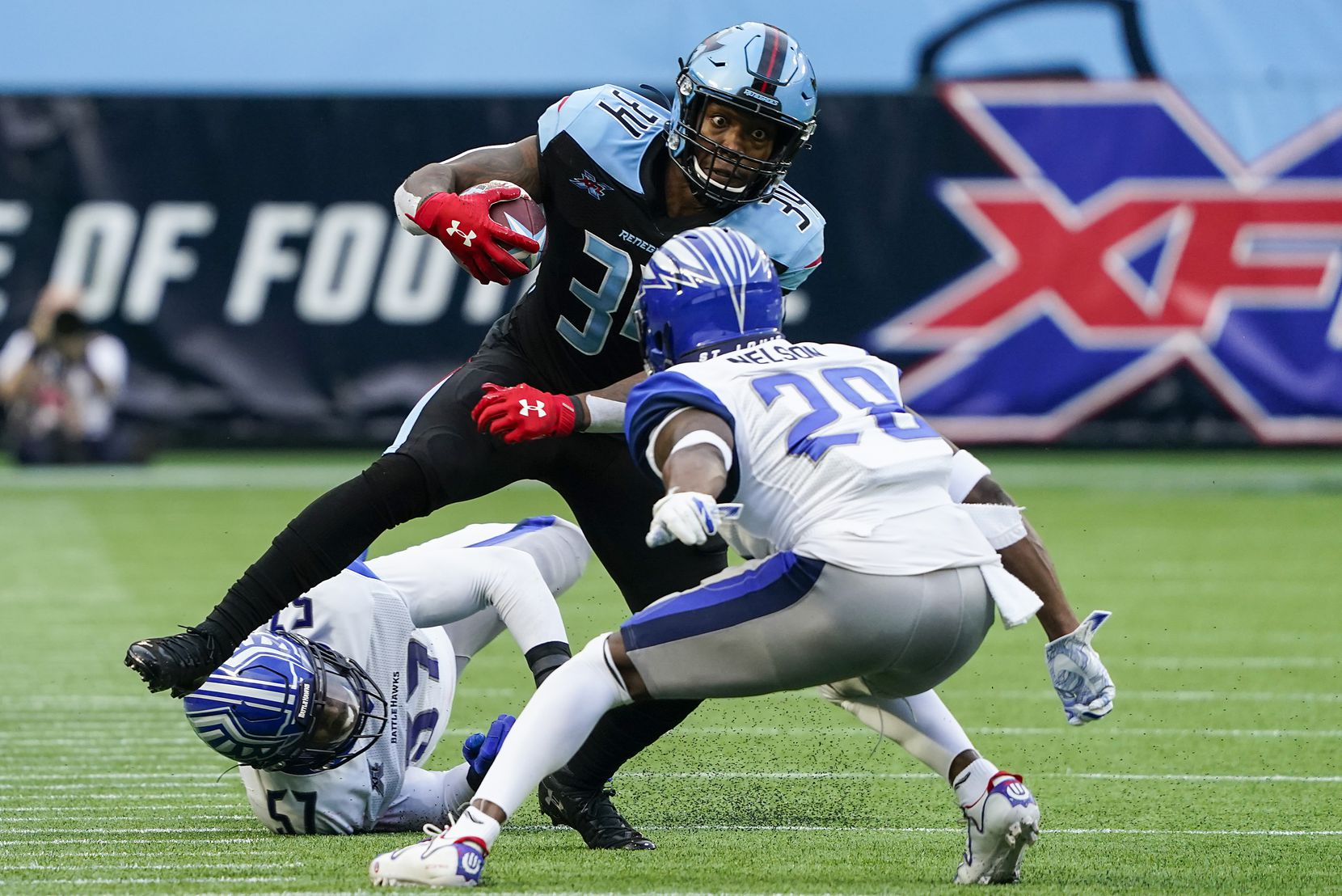 Dallas Renegades running back Cameron Artis-Payne (34) is brought down by St. Louis Battlehawks linebacker Terence Garvin (57) and cornerback Robert Nelson (28) during the first half of an XFL football game at Globe Life Park on Sunday, Feb. 9, 2020, in Arlington.