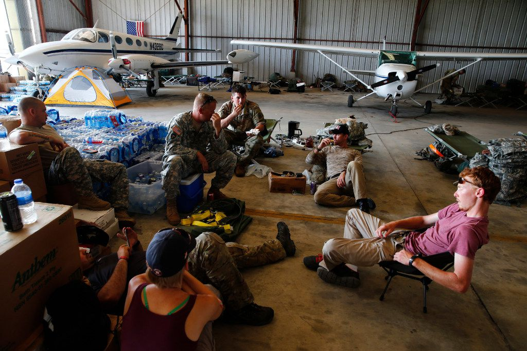 The Texas National Guard (4th Battalion, 133rd Regiment) takes a break from unloading cargo a week after Hurricane Harvey at the Orange County Airport in Orange, Texas, on Sept. 2, 2017.