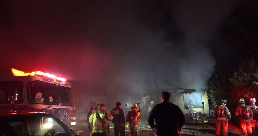 Dallas emergency workers respond to a house fire on Newcombe Drive on Sunday.