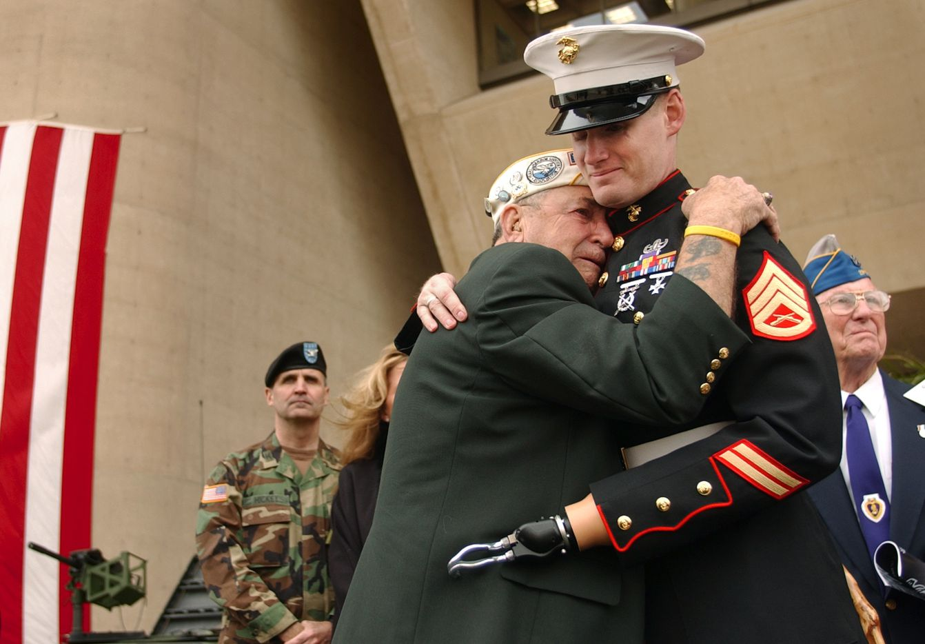 Pearl Harbor survivor Houston James of Dallas was overcome with emotion as he embraced former Marine SSgt. Mark Graunke Jr. of Flower Mound during the Dallas Veterans Day Commemoration on Nov. 10, 2004, at Dallas City Hall. Graunke, who was a member of a Marine ordnance-disposal team,  lost a hand, leg and eye while defusing a bomb in Iraq in July 2003.