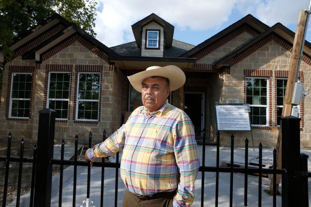 City Hall-backed housing developer Santos Coria stands in front of one of his houses on Pueblo Street in West Dallas.