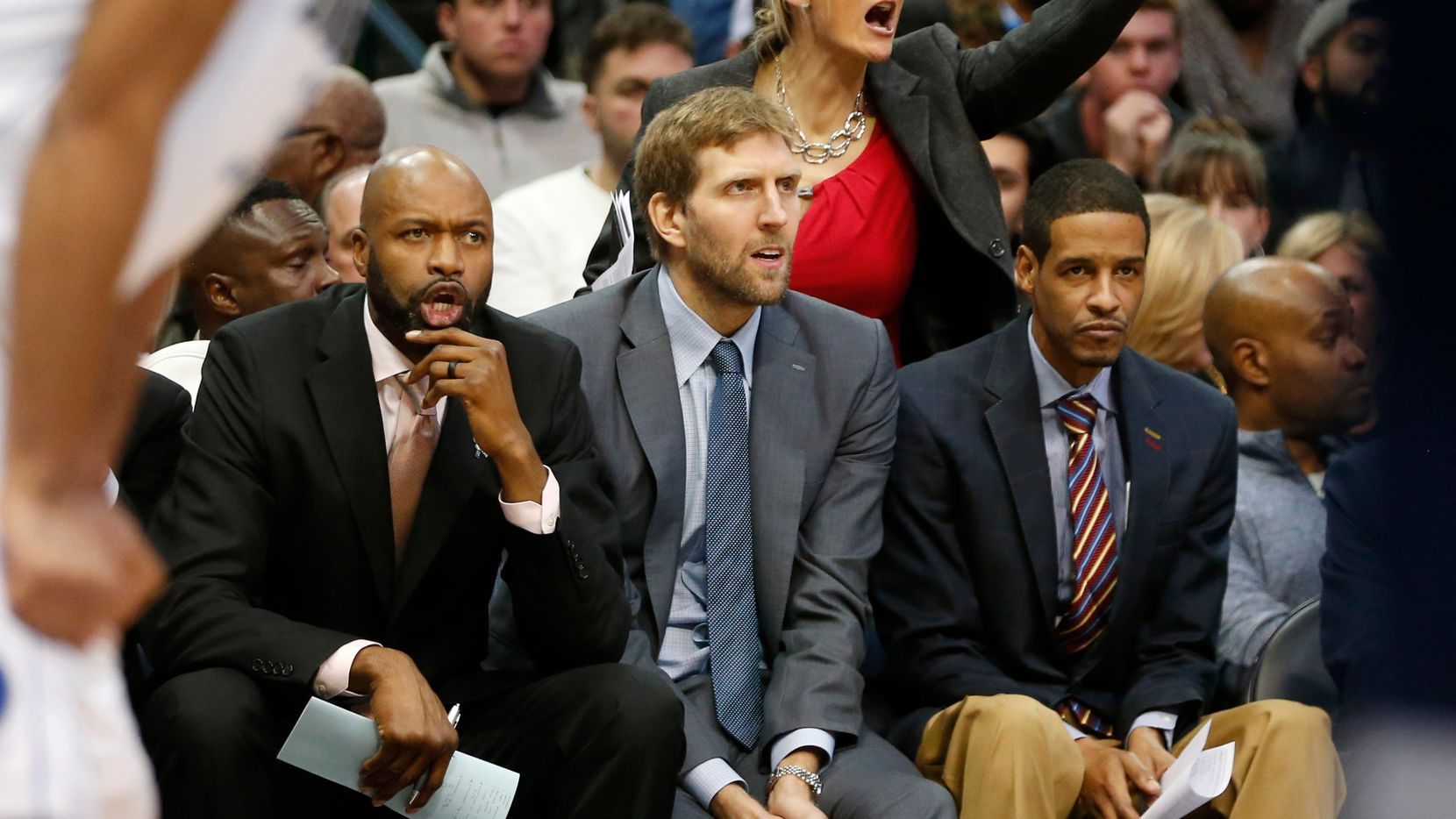 Dallas Mavericks assistant coaches Jamahl Mosley (left) and Stephen Silas sit alongside Dirk Nowitzki during a game against the Utah Jazz at American Airlines Center in Dallas on Wednesday, November 14, 2018.