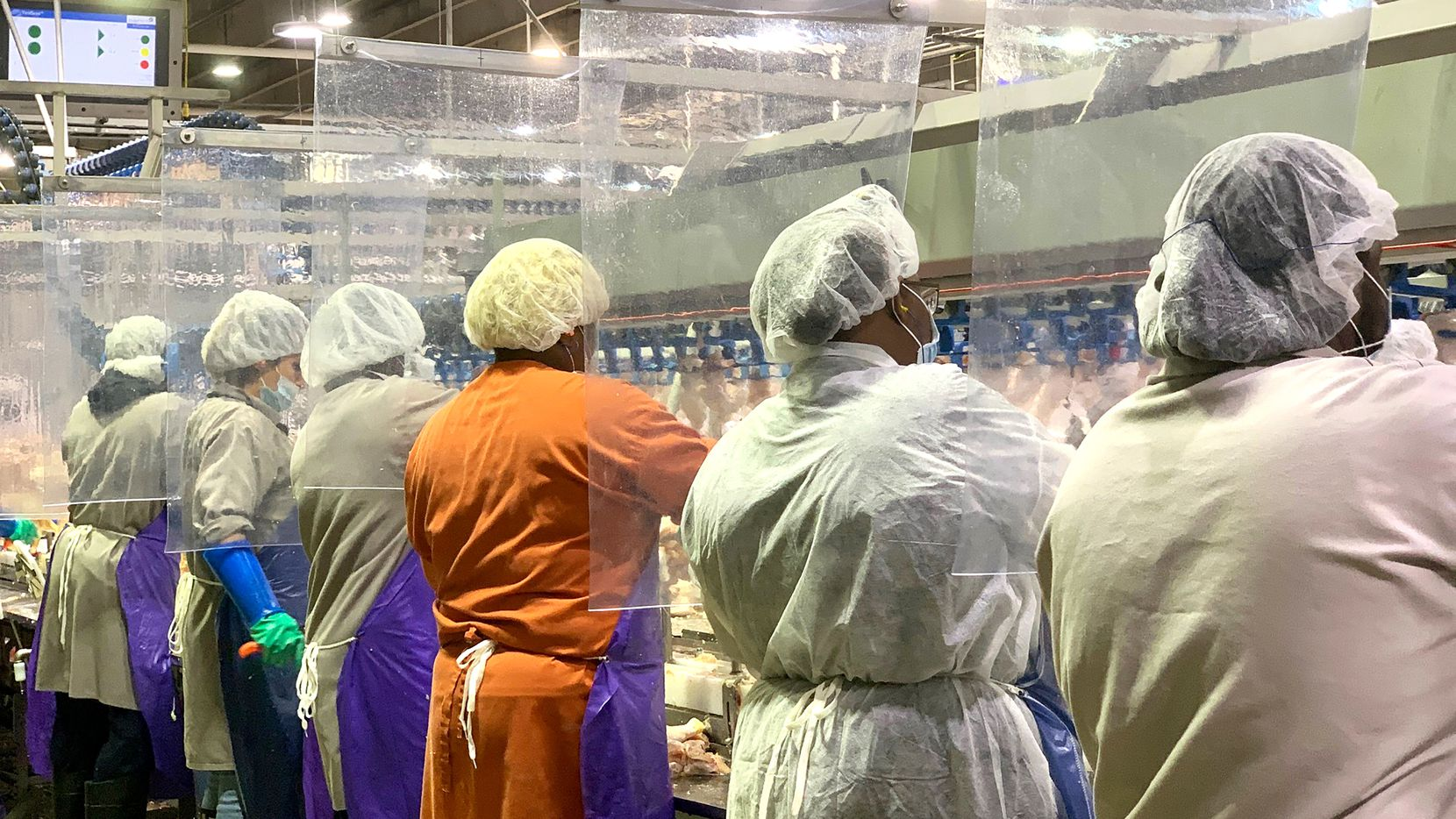 Two of Texas' top three counties for coronavirus prevalence have major meat-packing plants. Shown are Tyson Foods workers at a poultry processing plant in Camilia, Ga., plant who were outfitted with protective masks, standing between new plastic dividers added to create separation.