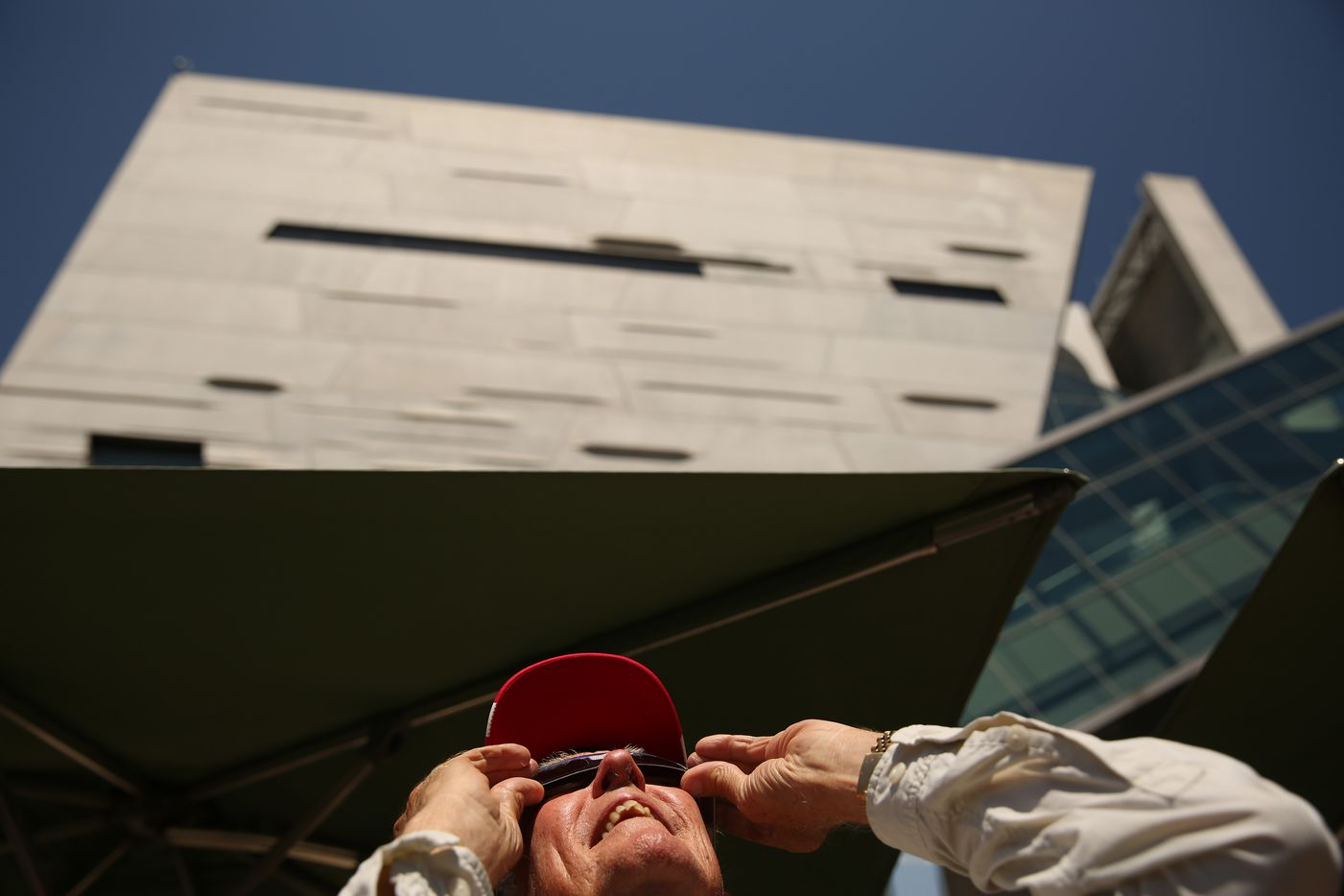 Hal Brown of Dallas looks at the sun during a solar eclipse outdoor watch party at the Perot Museum of Nature and Science.