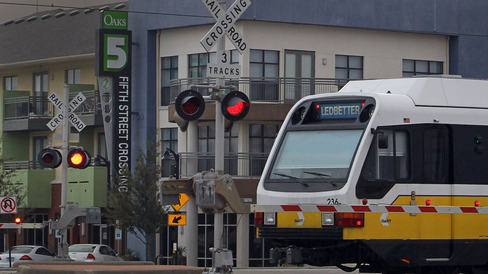 A DART train passes by the 5th Street Crossing residences, a transit-oriented mixed-use development, at the downtown Garland Blue Line station.