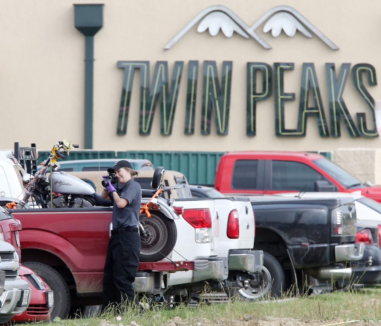 A law enforcement officer  photographed a vehicle in the parking lot of Twin Peaks in Waco last week. The shootout has put strains on McLennan County resources, and a judge is seeking help from public defenders in neighboring counties.