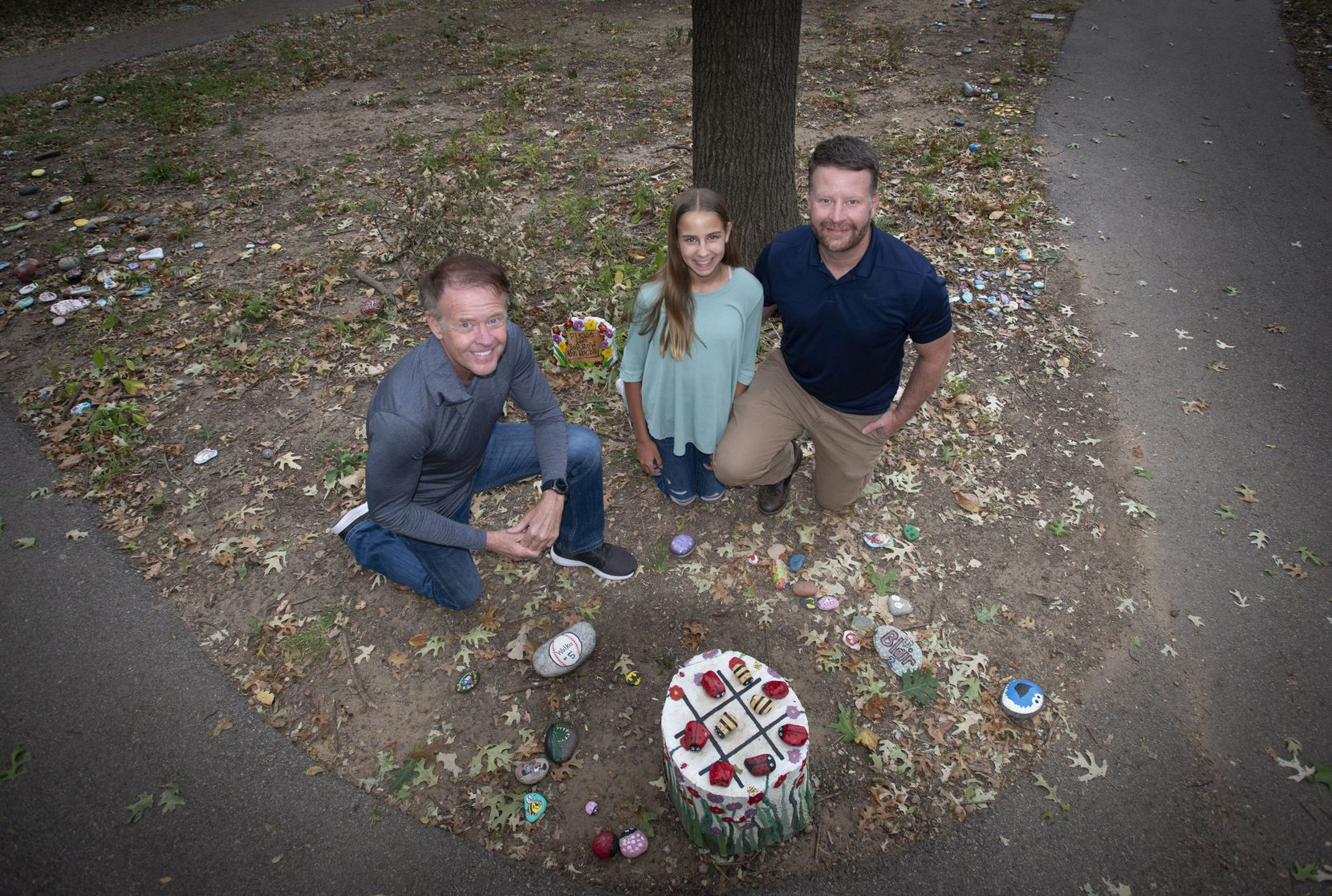 Ron Olsen, left, Sophia Penny (one of the first artists to contributer a rock) and her father Chris Penny on the rock art trail at Parr Park in Grapevine, Texas on October 15, 2020.