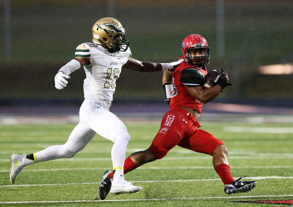 Cedar Hill's Kaegun Williams (24) attempts to break away from DeSoto's Isaiah Stewart (13) during the first half of play at Longhorn Stadium in Cedar Hill, on Friday, October 23, 2015. (Vernon Bryant/The Dallas Morning News)