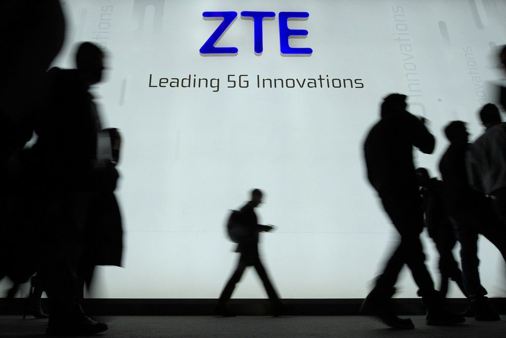 This file picture taken on February 27, 2018 shows people walking in front of the ZTE stand at the Mobile World Congress (MWC), the world's biggest mobile fair, in Barcelona.  Chinese telecom giant ZTE has its U.S. headquarters in Richardson. / AFP PHOTO / Lluis GENELLUIS GENE/AFP/Getty Images