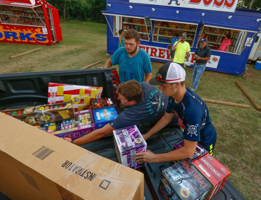 From left: Jeremiah Smith, Colton Taylor and Zane Taylor load up fireworks purchased by Cleve Magers (left background) and Tony Magers at Big Boss Fireworks along FM1187 near the western edge of Mansfield.