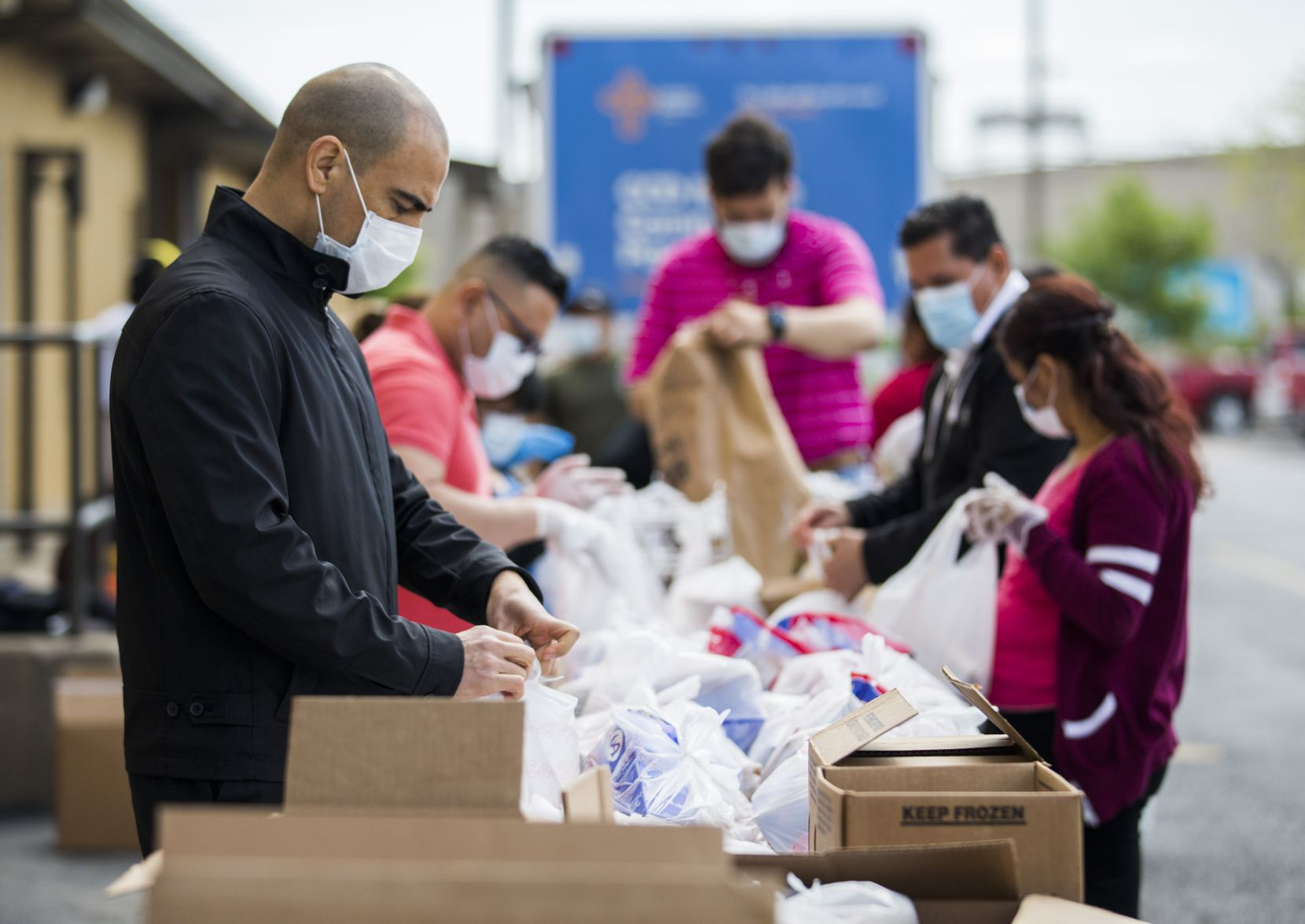 Rev. Jesus Belmontes (left) and other volunteers hand out food at San Juan Diego Catholic Church on Saturday, April 11, 2020 in Dallas.