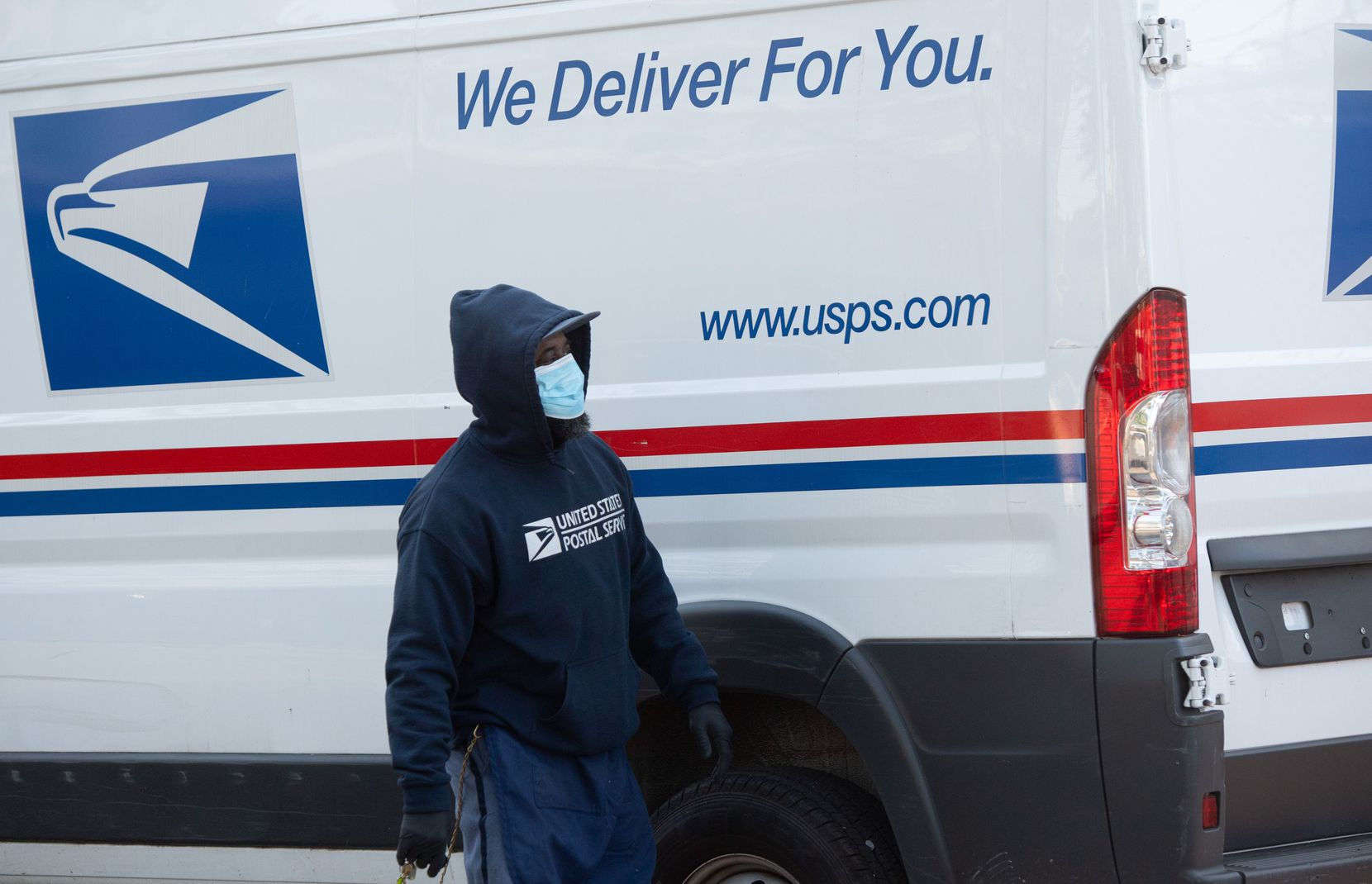 A postal worker wearing a face mask and gloves loads a truck with packages at a post office in Washington, D.C.