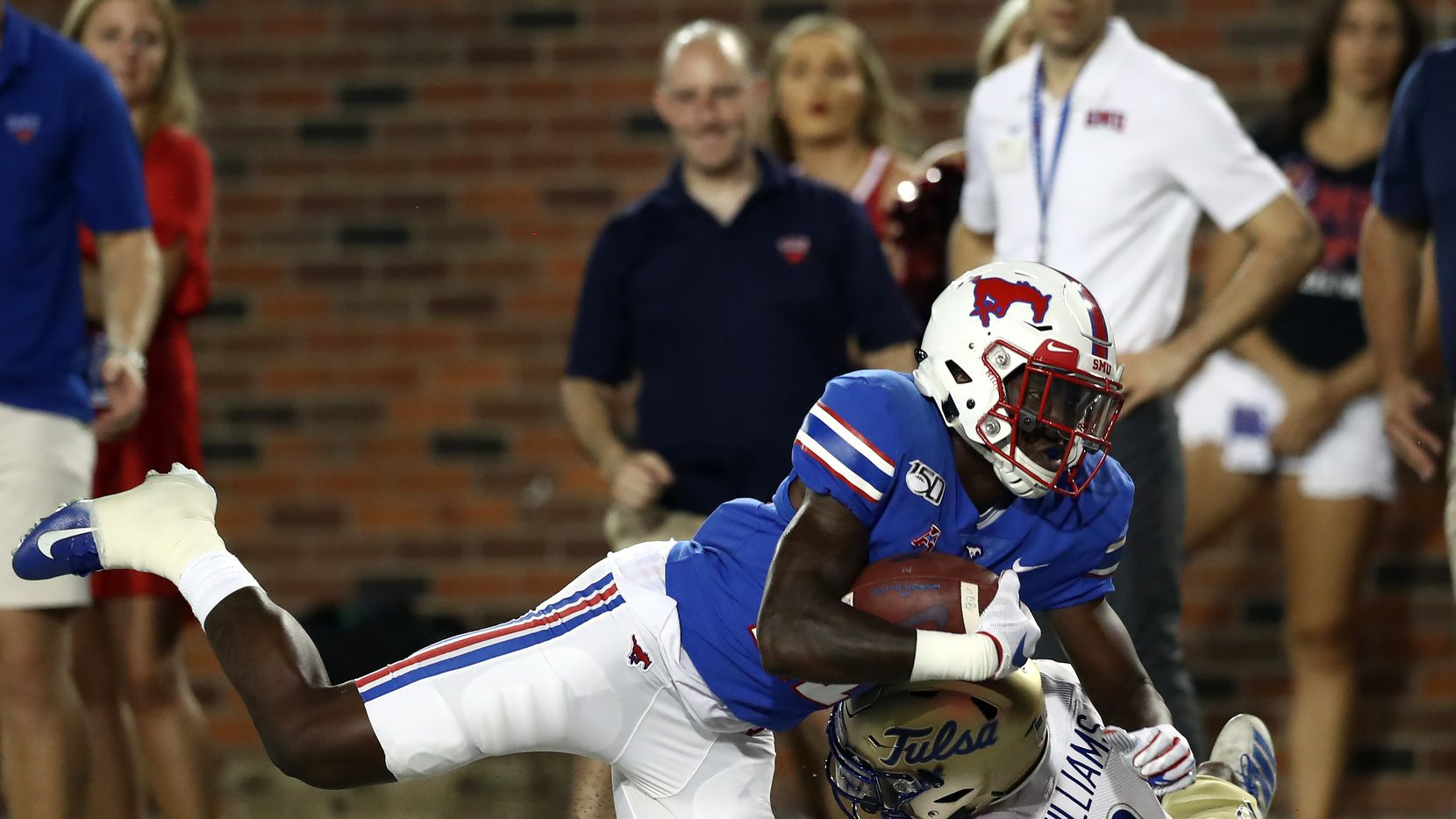 DALLAS, TEXAS - OCTOBER 05:  Rashee Rice #11 of the Southern Methodist Mustangs is tackled by Cristian Williams #3 of the Tulsa Golden Hurricane in the third quarter at Gerald J. Ford Stadium on October 05, 2019 in Dallas, Texas. (Photo by Ronald Martinez/Getty Images)