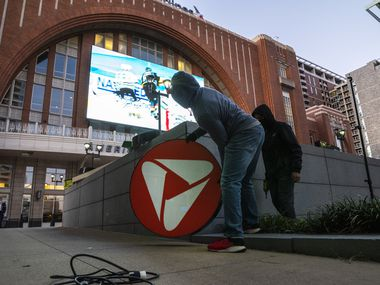 Sherrod Dickson of Dickson Signs prepares to lift a portion of signage containing the PNC Bank logo as a crew physically renames Victory Plaza to PNC Plaza outside the American Airlines Center in Dallas.