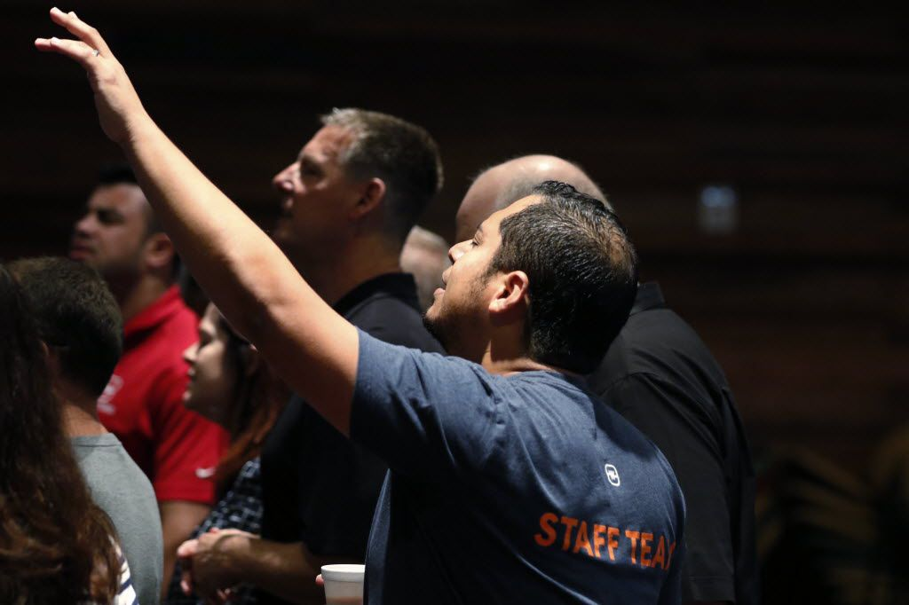 Oscar Castillo, right, and Todd Wagner, center, sing during the Tuesday Staff Prayer meeting.