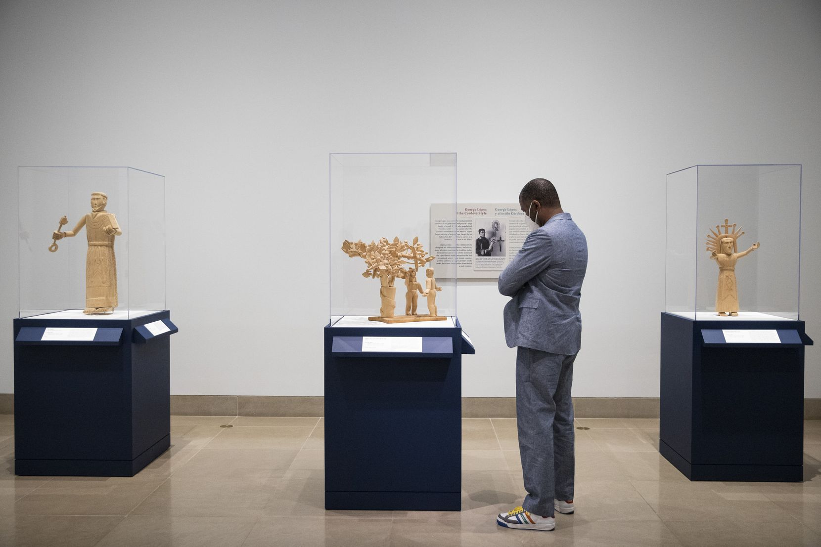 """John Spriggins views a trio of pieces by artist George Lopez in the """"Devoted: Art and Spirituality in Mexico and New Mexico"""" exhibition at the Dallas Museum of Art."""