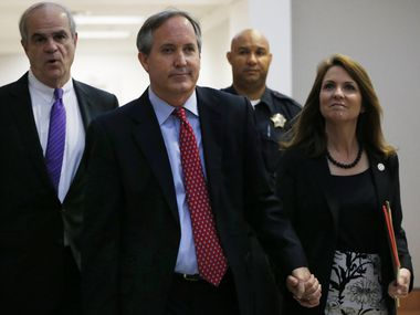 Texas Attorney General Ken Paxton and his wife Angela Paxton enter the Merrill Hartman Courtroom in the Fifth Court of Appeals at the George Allen Courts Building in Dallas on May 12, 2016. Paxton has been facing three felony fraud indictments since July 2015 but has not yet faced trial. (Rose Baca/The Dallas Morning News)